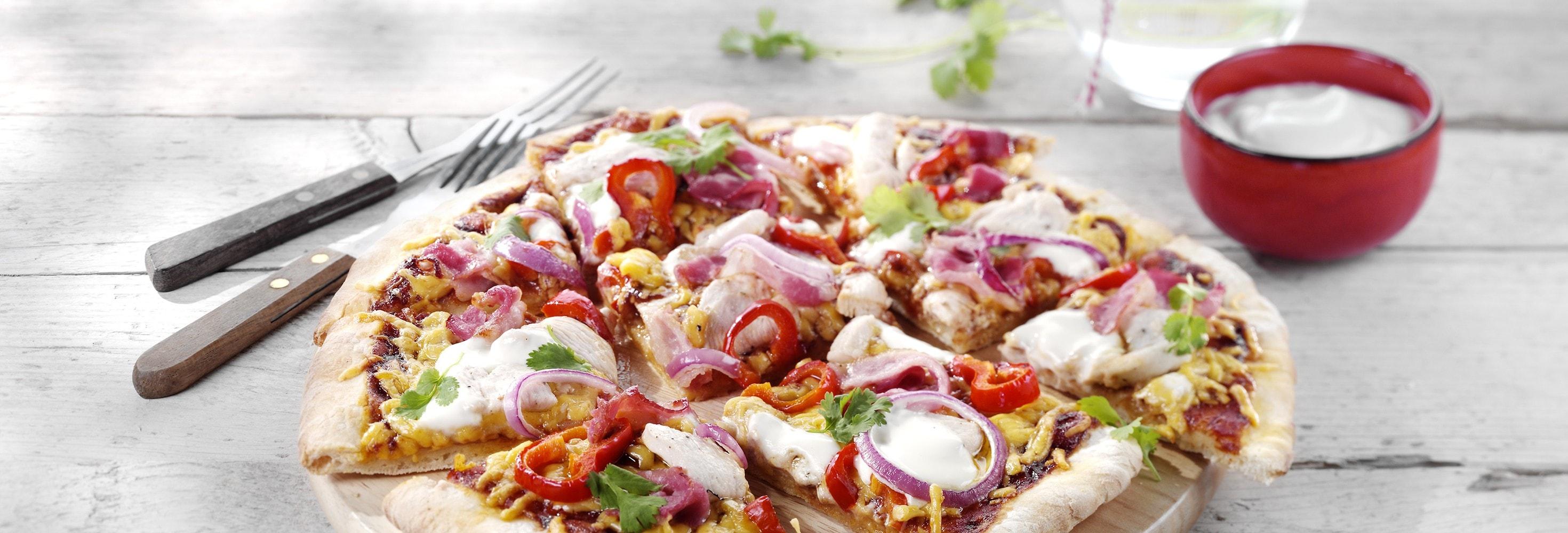 Pizza met pittige kip, koriander en een dressing van zure room