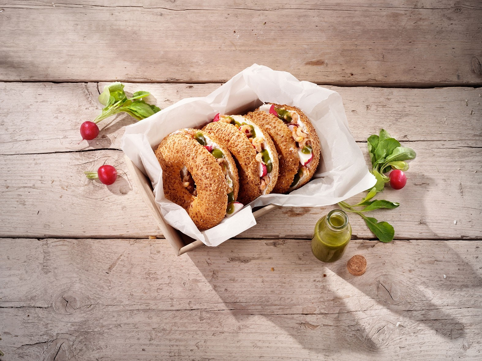 Bagel met plattekaas, garnalen, radijs en waterkersdressing